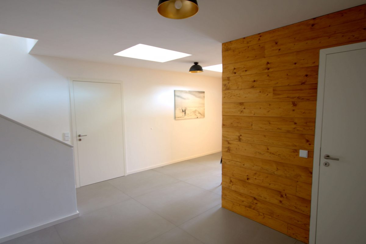 Flur inkl. Wandverkleidung aus Altholz (gebürstet und gehackt), Innentüren stumpf einschlagend flächenbündig in Wandverkleidung integriert und begehbare Oberlichter als Lichtquelle