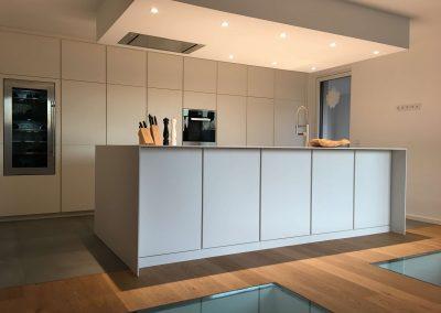 Küche weißlack matt mit eingefrästen Griffleisten und FENIX Arpa Arbeitsplatte - Küchengeräte von Miele - Deckensegel inkl. LED Beleuchtung, begehbare Glasböden