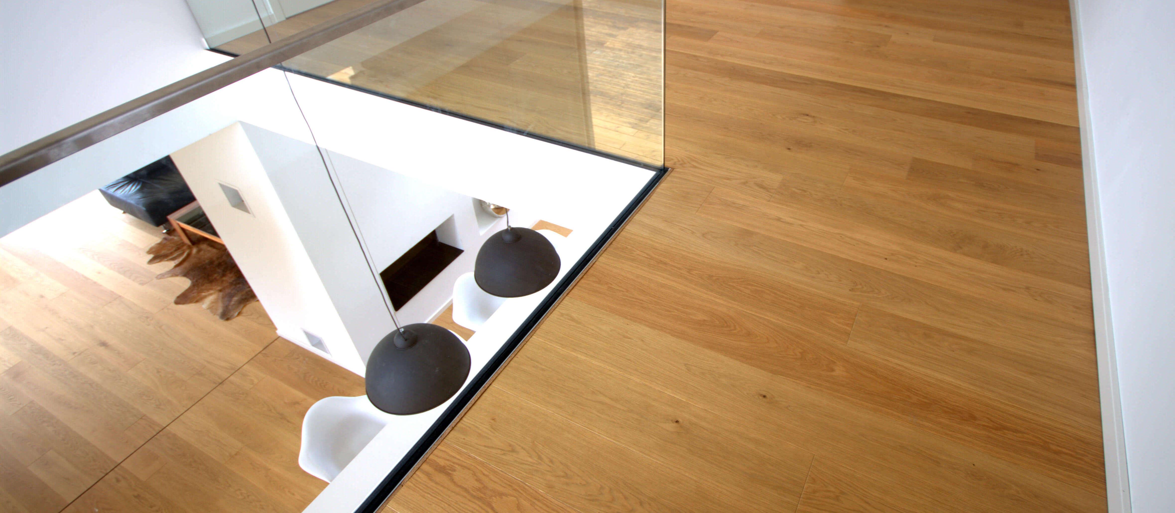 Galerie, Couchtisch aus Nussbaum Massivholz, HARO Eiche Landhausdiele, in Boden eingelassene Glasbrüstung und Esstisch