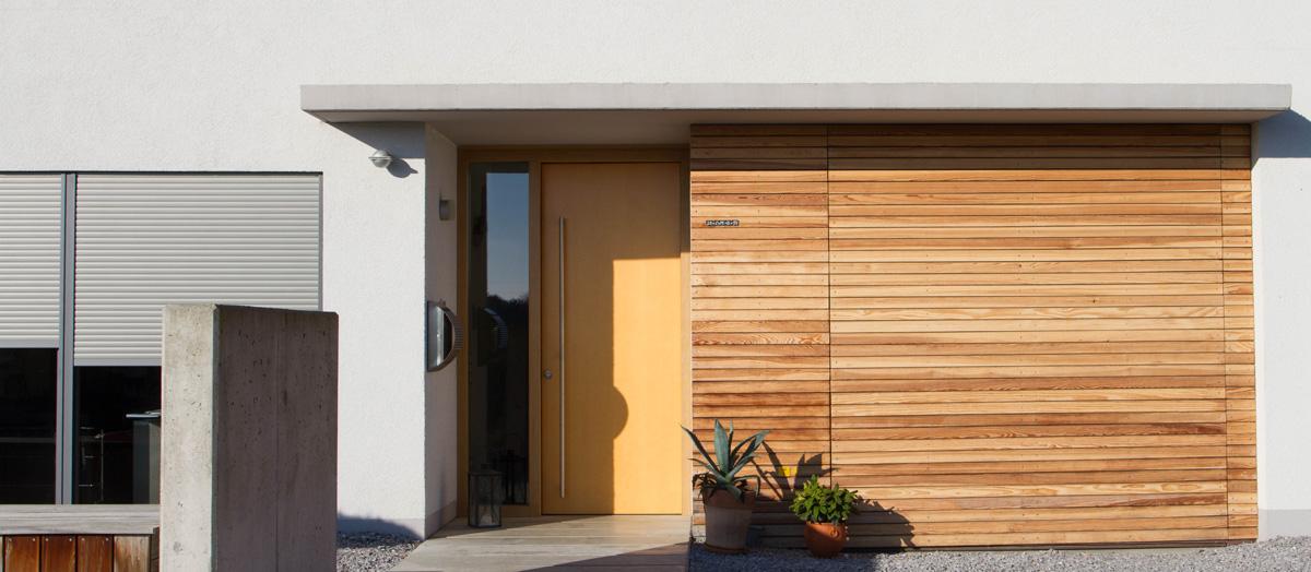 Holz-Haustür und flächenbündiges Garagentor mit Holz verkleidet