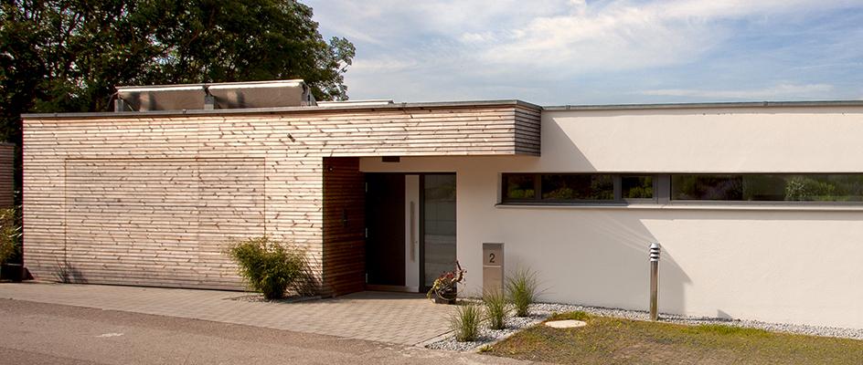 Aluminium-Haustür von Kneer-Südfenster und anschließender Holzfassade mit flächenbündigem Garagentor